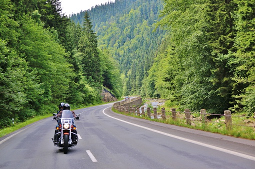 Two people riding a motorcycle on a rural road