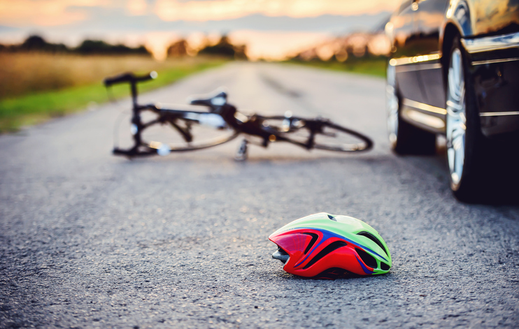 traffic accident between a car and a bicycle with helmet in road